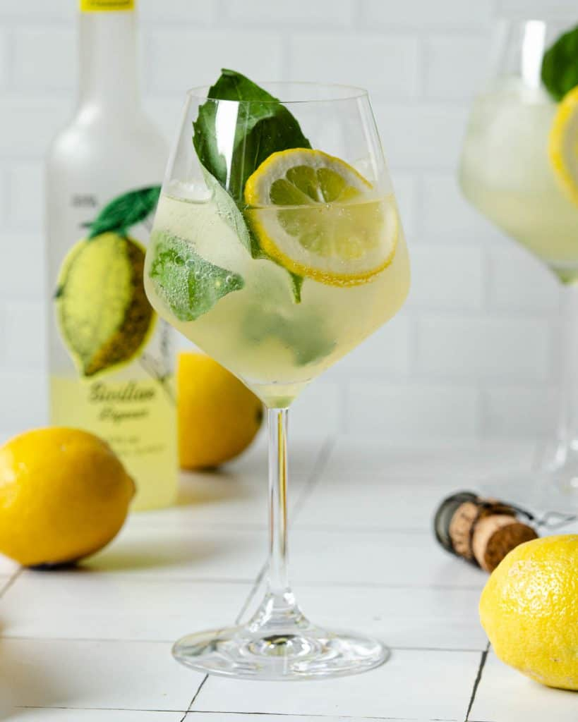 straight on photo of a limoncello spritz with a bottle of limoncello in the back left and lemons