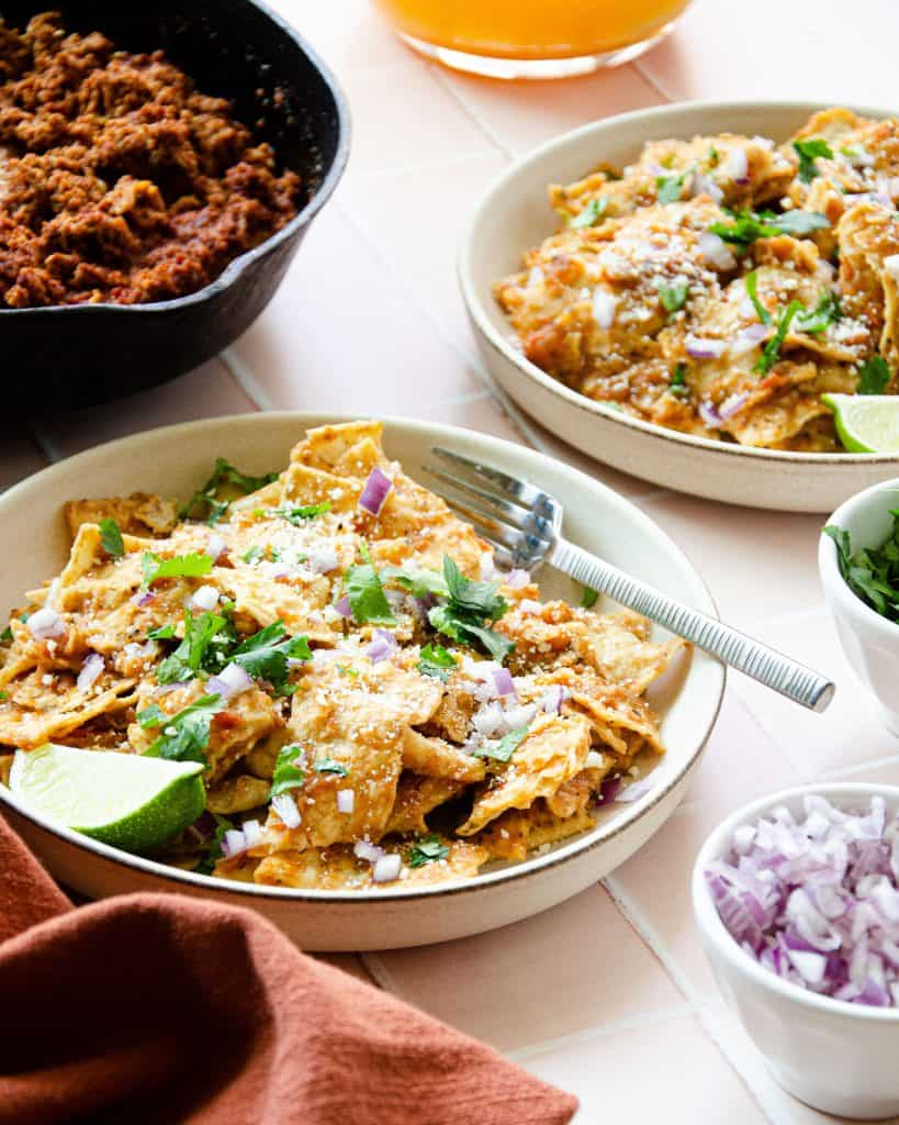 two plates of chilaquiles rojos with a cast iron of chorizo and eggs on the side