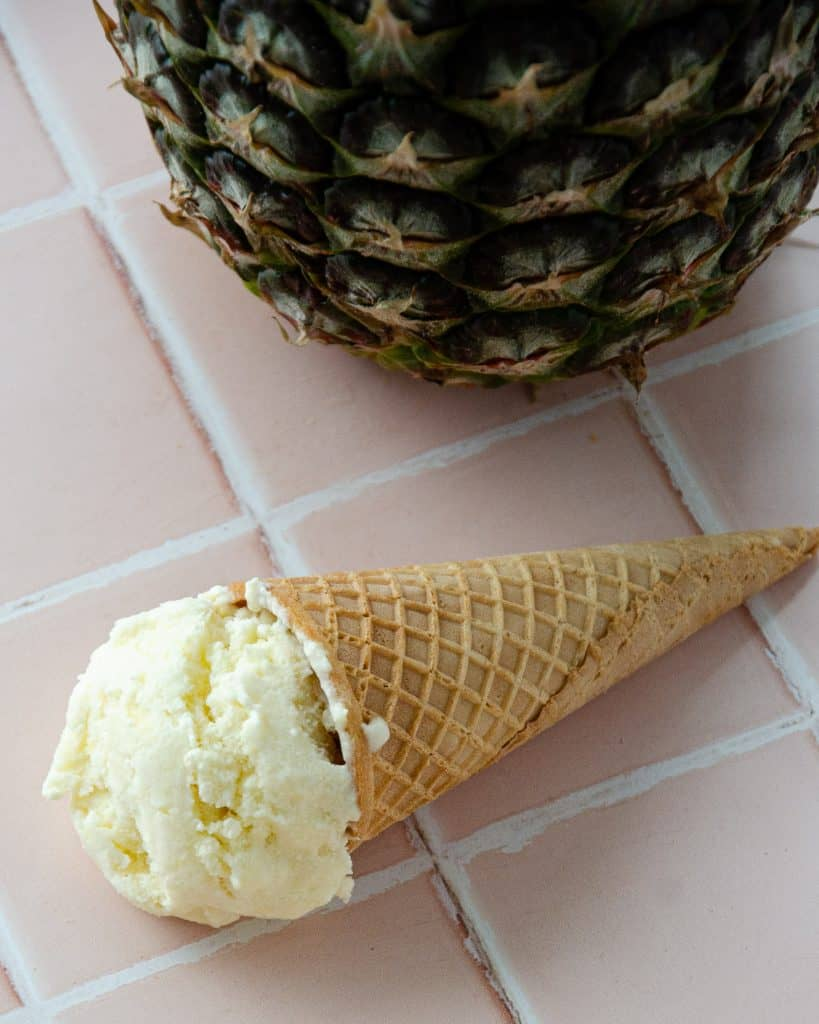 coconut pineapple ice cream in a cone on top of tile with a pineapple hidden in the back