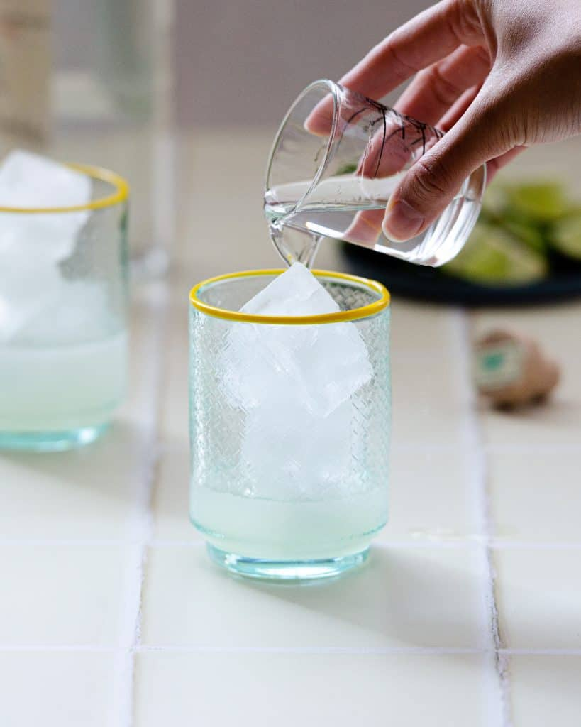 pouring tequila into a ranch water cocktail