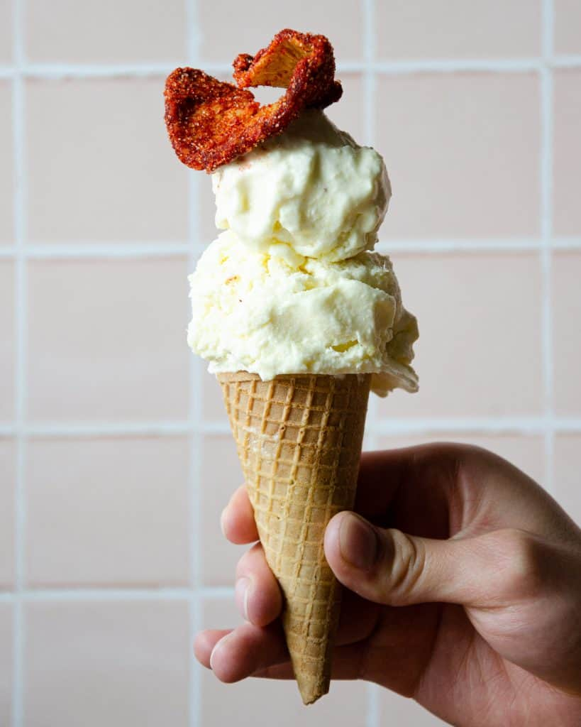 a hand holding an ice cream cone with two scoops of ice cream and a chile dried pineapple piece on top.