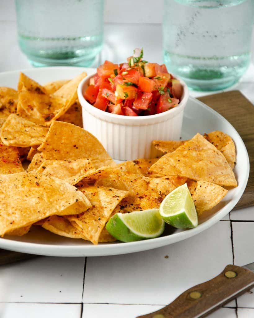 a side view of a plate filled with tortilla chips and a bowl of pico de gallo with two cups in the back