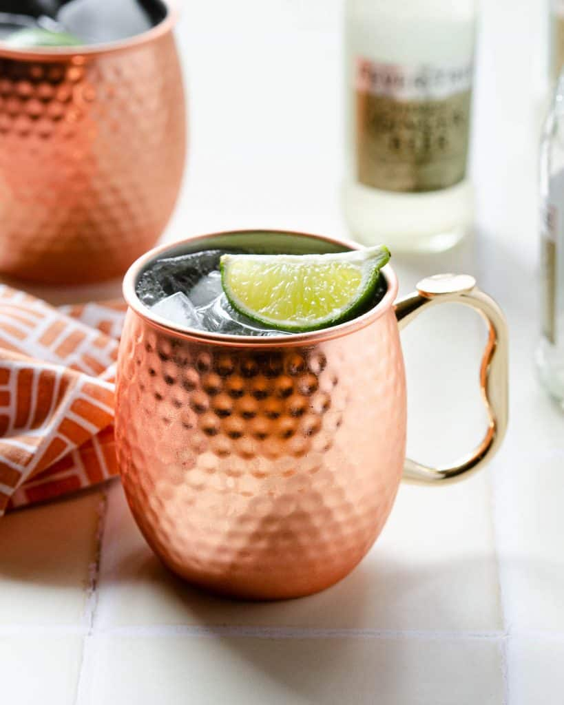 a copper mug filled with a mexican mule and garnishes with a lime wedge with another mexican mule in the background