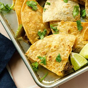 side view of carne asada quesadillas cut into quarters. quesadillas are on a baking sheet with cilantro and lime