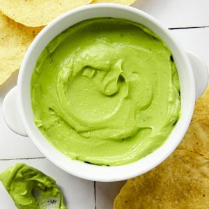 a bowl of whipped avocado surrounded by chips and a spoon of green creamy sauce