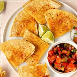 square image of overhead of complete quesadilla on a white plate with a bowl of pico de gallo and limes on top. lime wedges in the corner and a spoon of pico de gallo on the side.