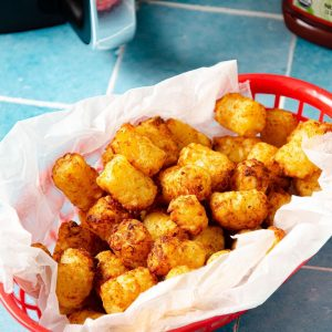 tater tots in a red basket with an air fryer in the back and a ketchup bottle out of sight