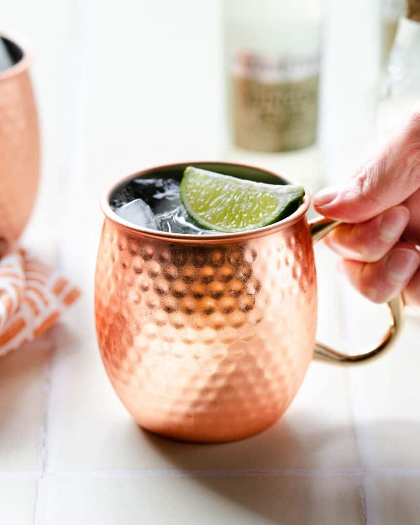 a hand grabbing a tequila mule garnishes with a lime wedge in a copper mug