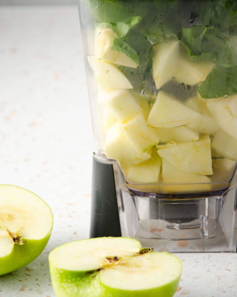 close up of green apple and spinach in a blender