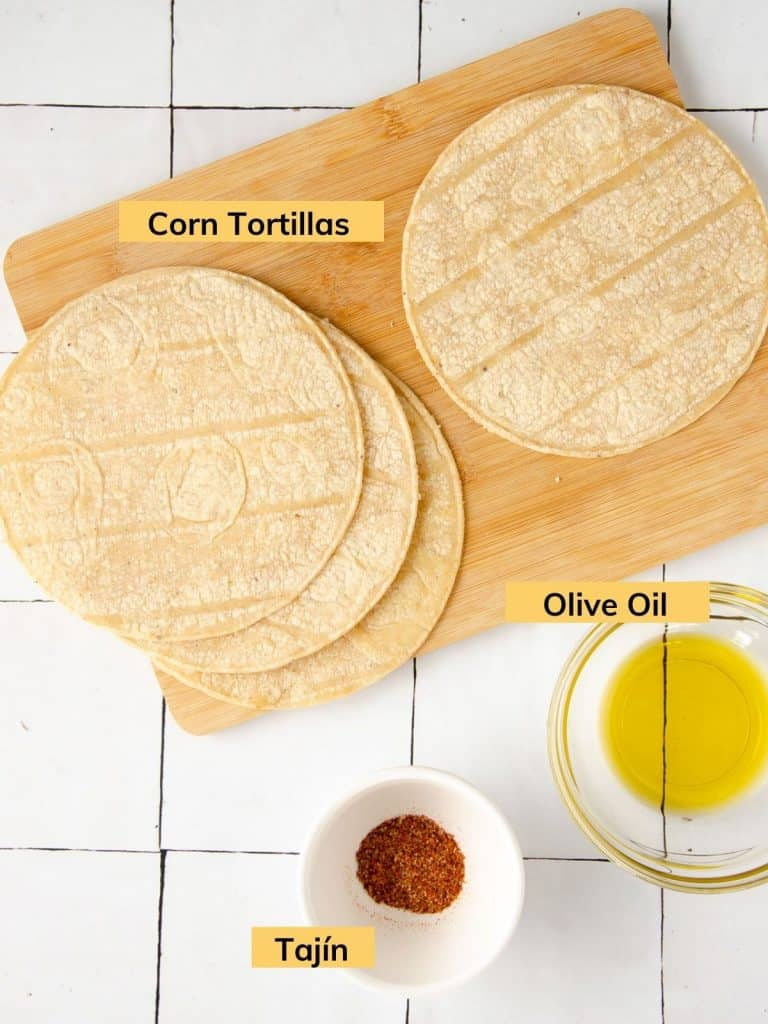 corn tortillas, a bowl of tajin and a bowl of olive oil on a tile countertop