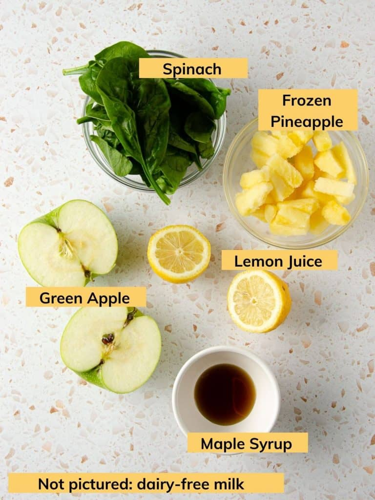 ingredients shot of spinach, green apples, frozen pineapple, lemons and maple syrup