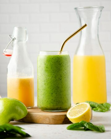 different juices and smoothies in bottles of varying height in yellow, orange and green. a lemon slice and half of a green apple in front