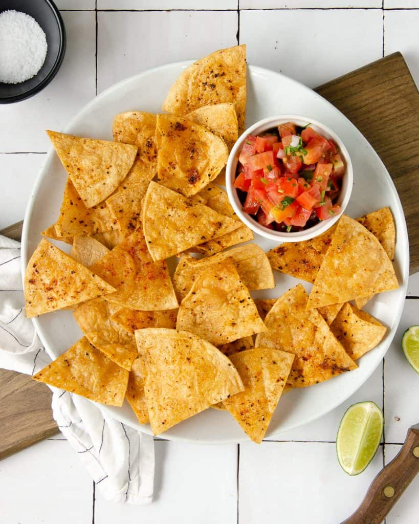 an overhead photo of a white plate topped with chili lime tortilla chips and a bowl of pico de gallo with limes scattered