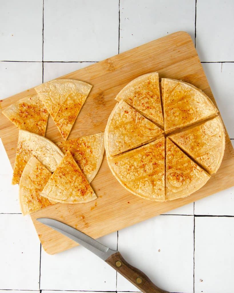 tortillas being cut into six even pie-slice like pieces on a cutting board with a knife