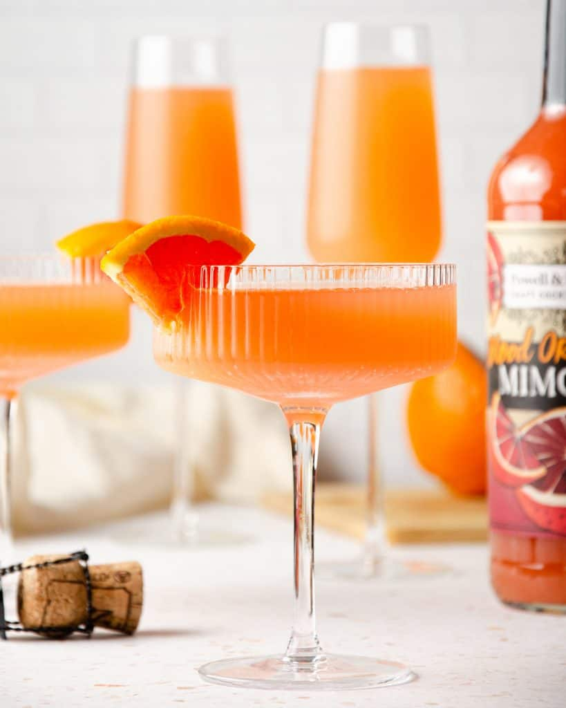coupe glasses filled with blood orange mimosa and topped with orange slices and two tall champagne glasses