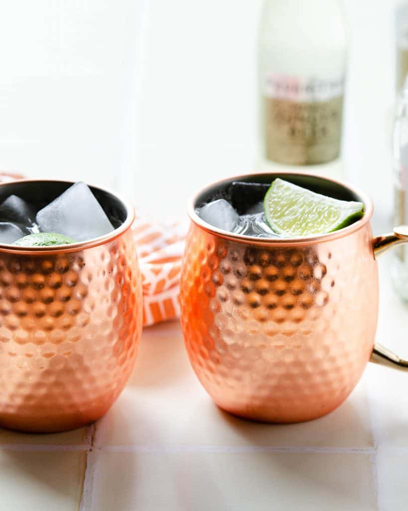 two tequila mules with ice and lime wedges with ginger beer bottles in the back