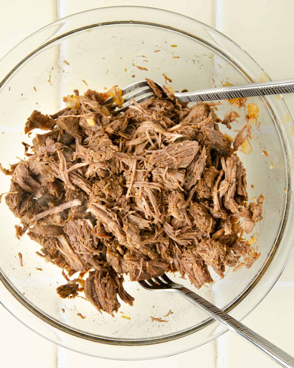 shredding chuck roast after simmering in the barbacoa seasoning and sauce. Use two forks to shred.