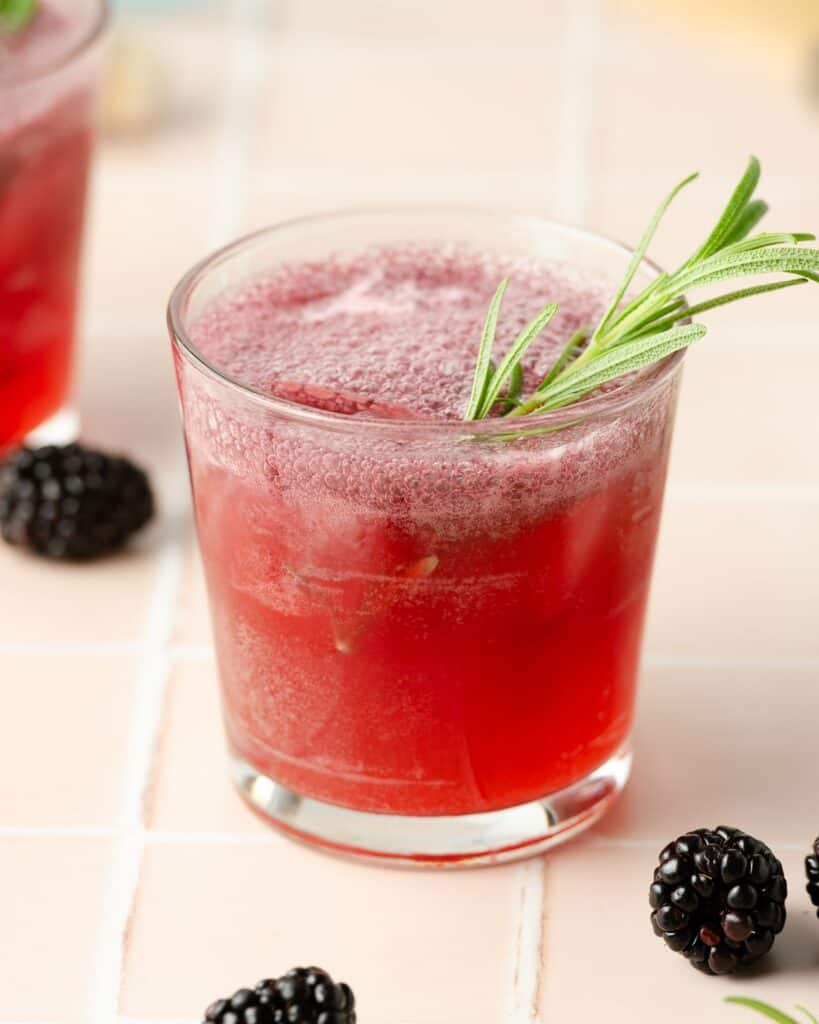 a close up shot of blackberry rosemary margarita garnished with fresh rosemary