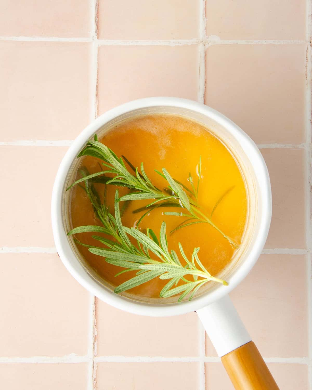 rosemary sprigs inside a pot of honey and water. the pot cools with the rosemary sprigs to take on a rosemary taste.