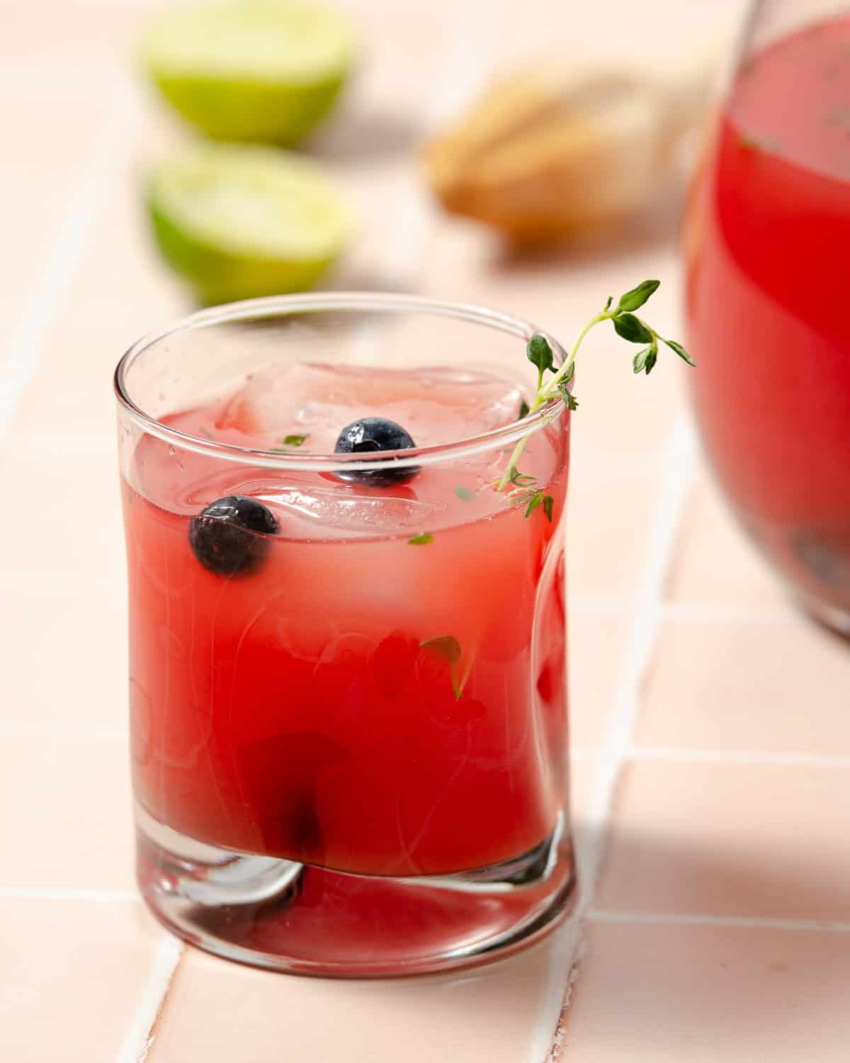 a close up of a glass of watermelon vodka punch with some blueberries and thyme decorating the glass. A large pitcher to the back right and two squeezed limes to the left