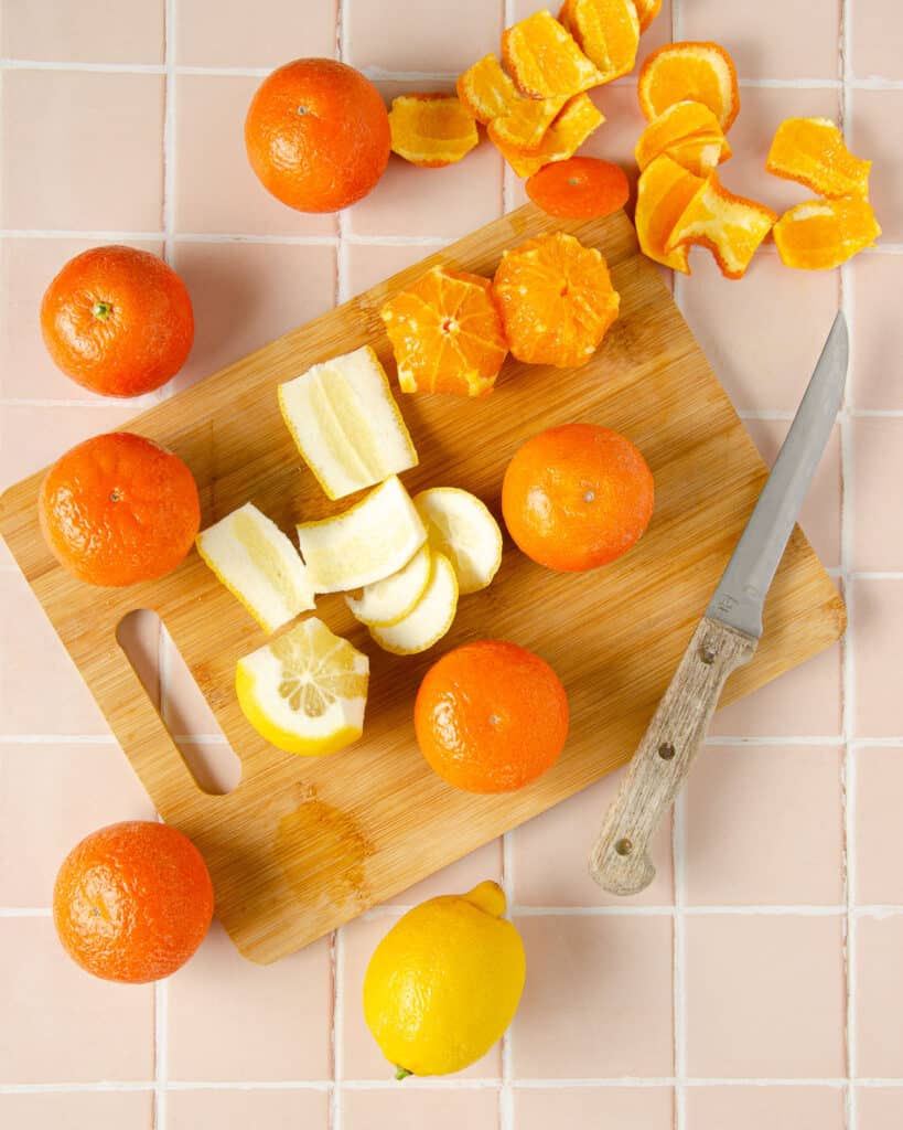 cutting mandarins and lemons on a wooden cutting board with peels and a wooden knife to the side
