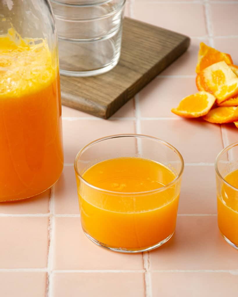 two small glasses of homemade mandarin juice with a pitcher of mandarin juice to the left side and mandarin peels in the back