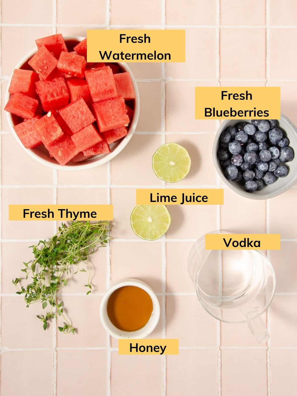 ingredients for a watermelon blueberry vodka smash pitcher: a bowl of fresh cubed watermelon, a bowl of fresh blueberries, a lime cut in half, fresh thyme sprigs, a cup of honey, and a measuring cup of vodka