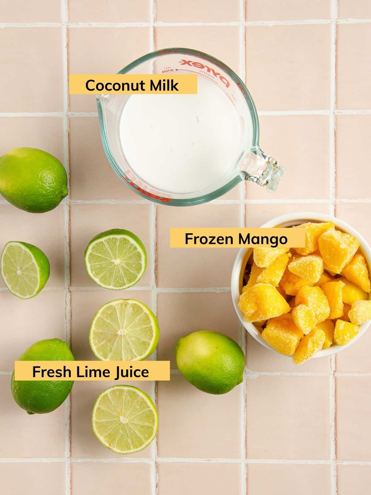 a measuring cup of coconut milk, a bowl of frozen mango chunks and halved limes on a countertop