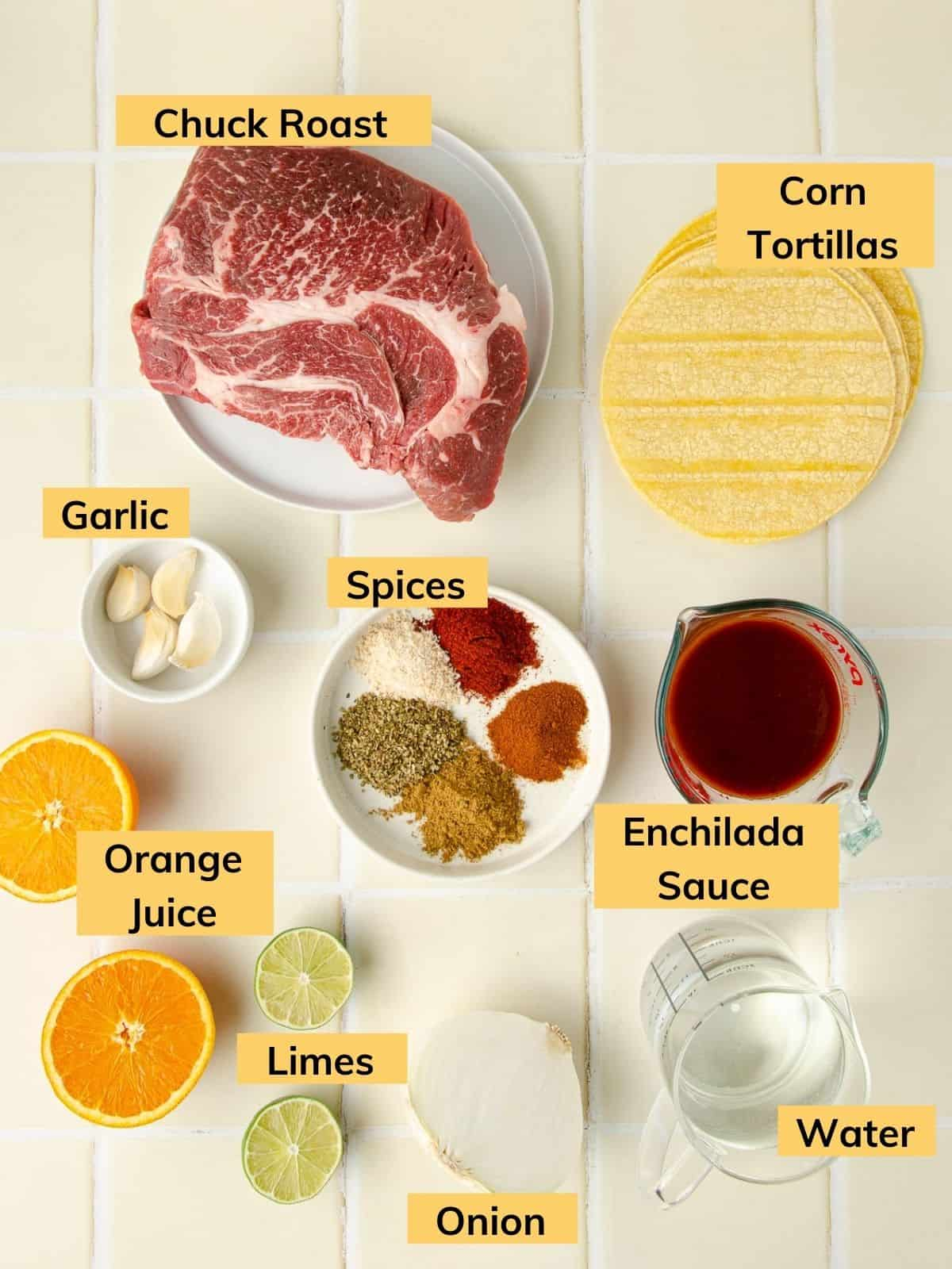 ingredients shot for barbacoa tacos: chuck roast, corn tortillas, enchilada sauce, water, half an onion, limes, orange juice, garlic cloves, and spices on a plate