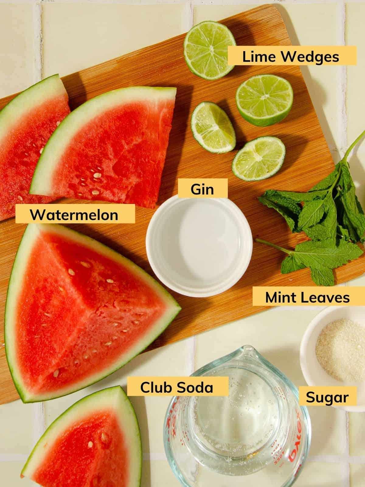 ingredients for a watermelon gin mojito: a watermelon cut into wedges, some lime wedges, fresh mint leaves, gin in a white ramekin, granulated sugar in a white bowl, and club soda in a glass measuring cup