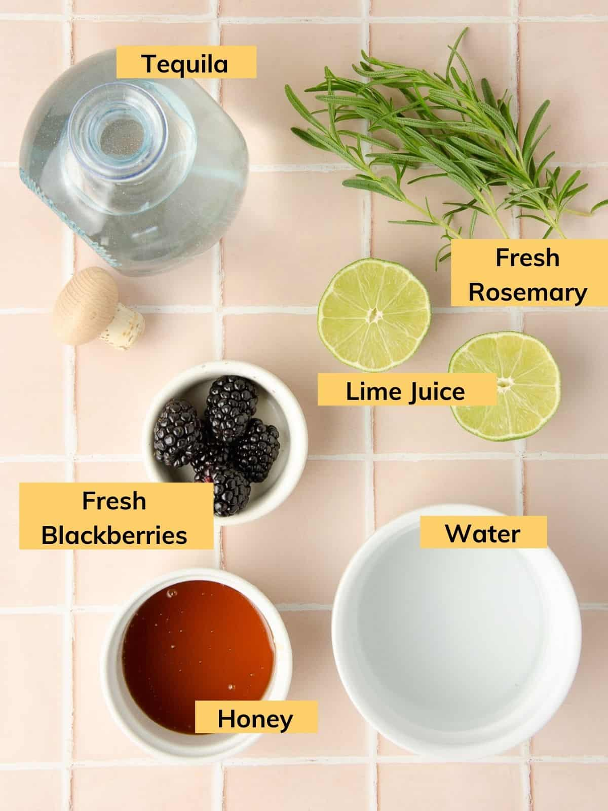 ingredients for a blackberry rosemary margarita - a bottle of tequila, fresh rosemary sprigs, a lime cut in half, fresh blackberries, water and honey in a bowl