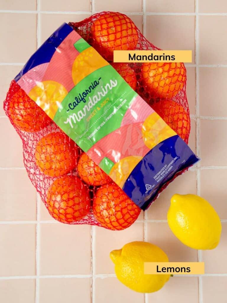 a bag of california mandarins and two lemons on a pink tile backdrop