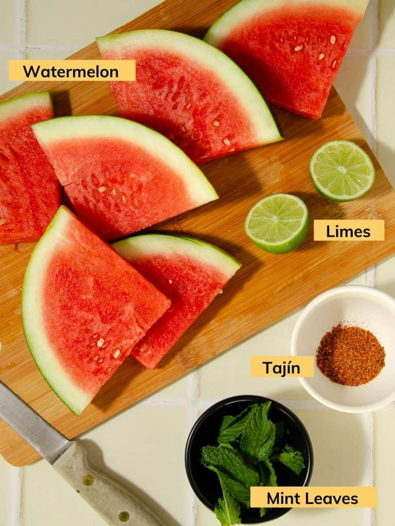 ingredients shot - sliced watermelon, halved limes, a bowl of mint leaves and tajin with a wooden knife