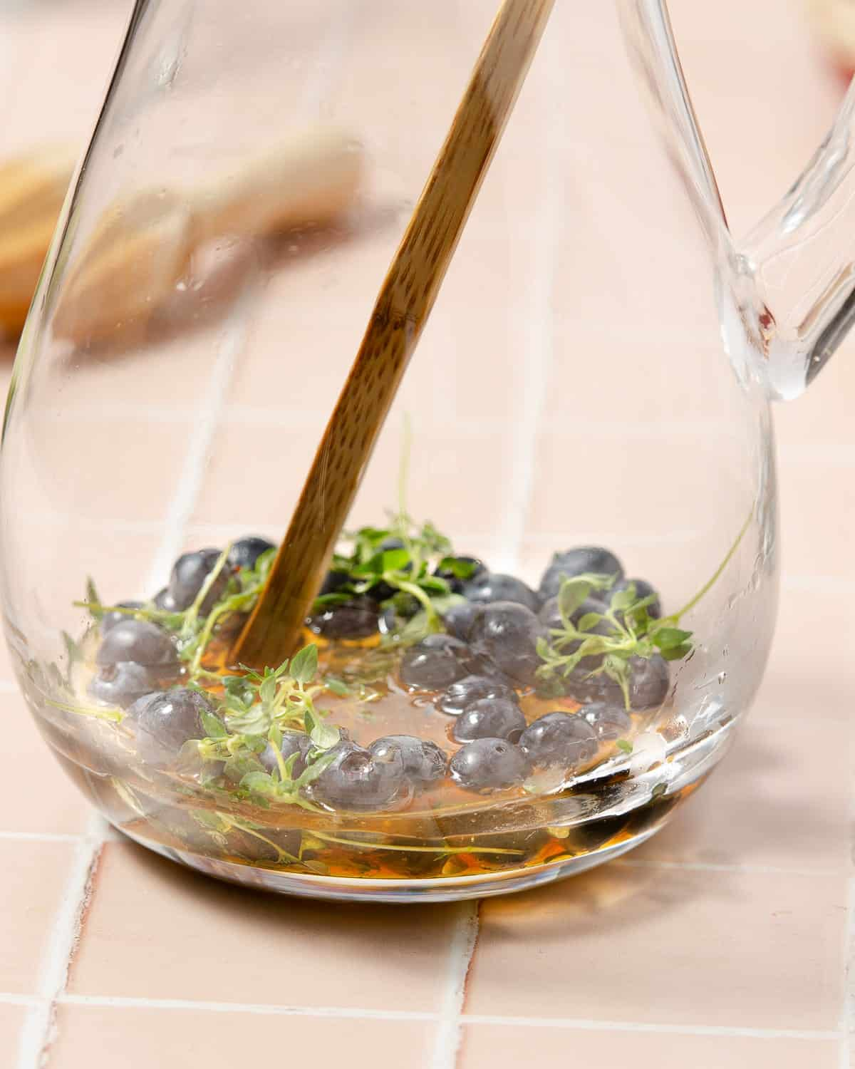 muddling blueberries, thyme and honey in a pitcher
