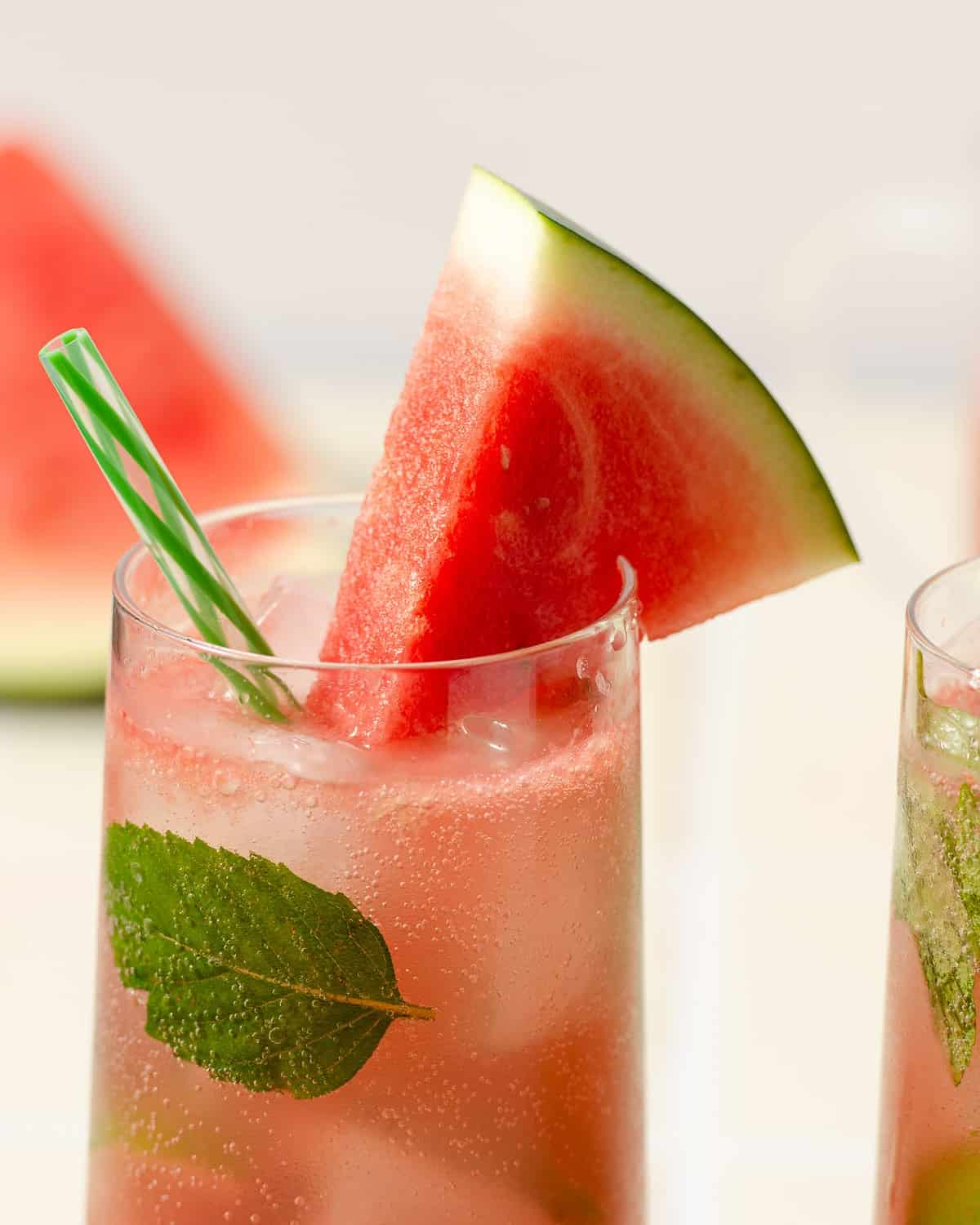 close up shot of a watermelon wedge sitting on a highball glass filled with a pink watermelon gin mojito with a light green striped straw and mint leaves