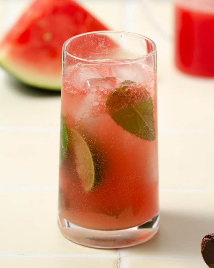 a pink watermelon gin mojito that is finished and filled with mint leaves and lime wedges