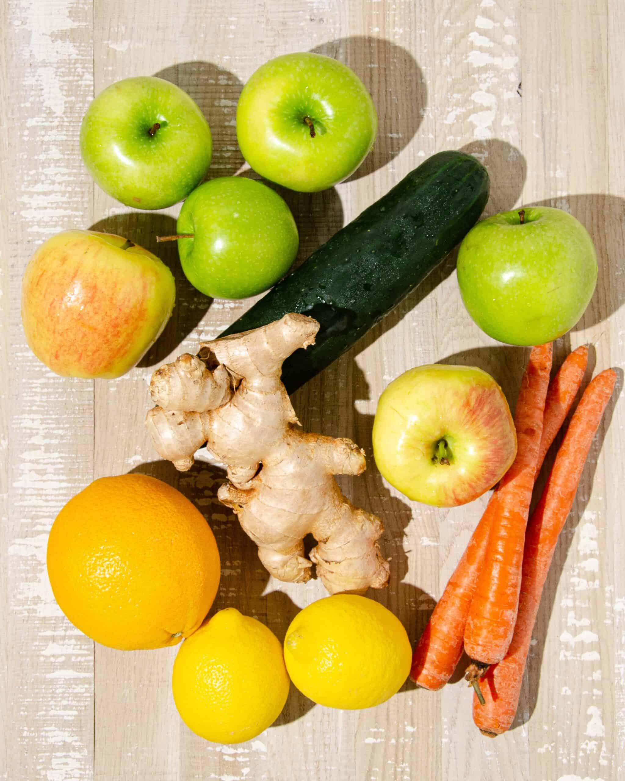 ingredients for juicer recipes for energy, including green apples, cucumber, ginger, carrots, apples, oranges and lemons.