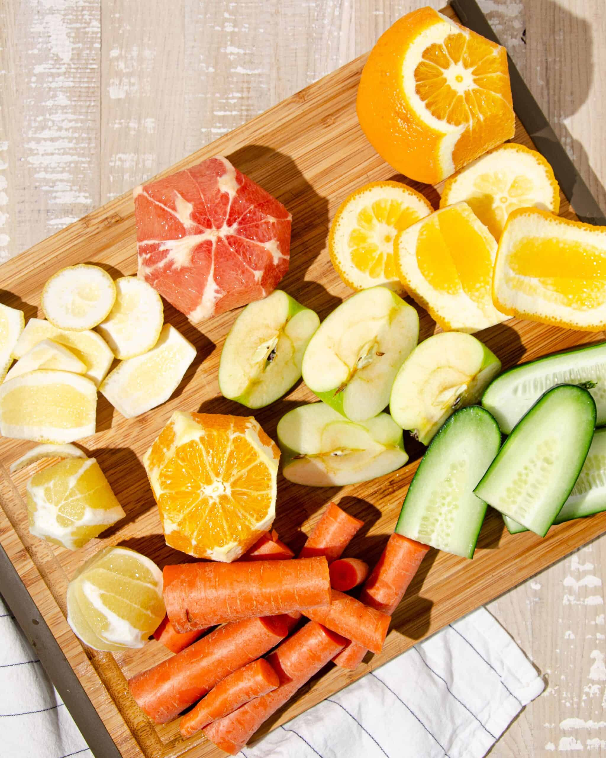 chopped ingredients for juicing - quartered green apples, peeled oranges, grapefruit and lemons, chopped cucumbers, and rough chopped carrots.