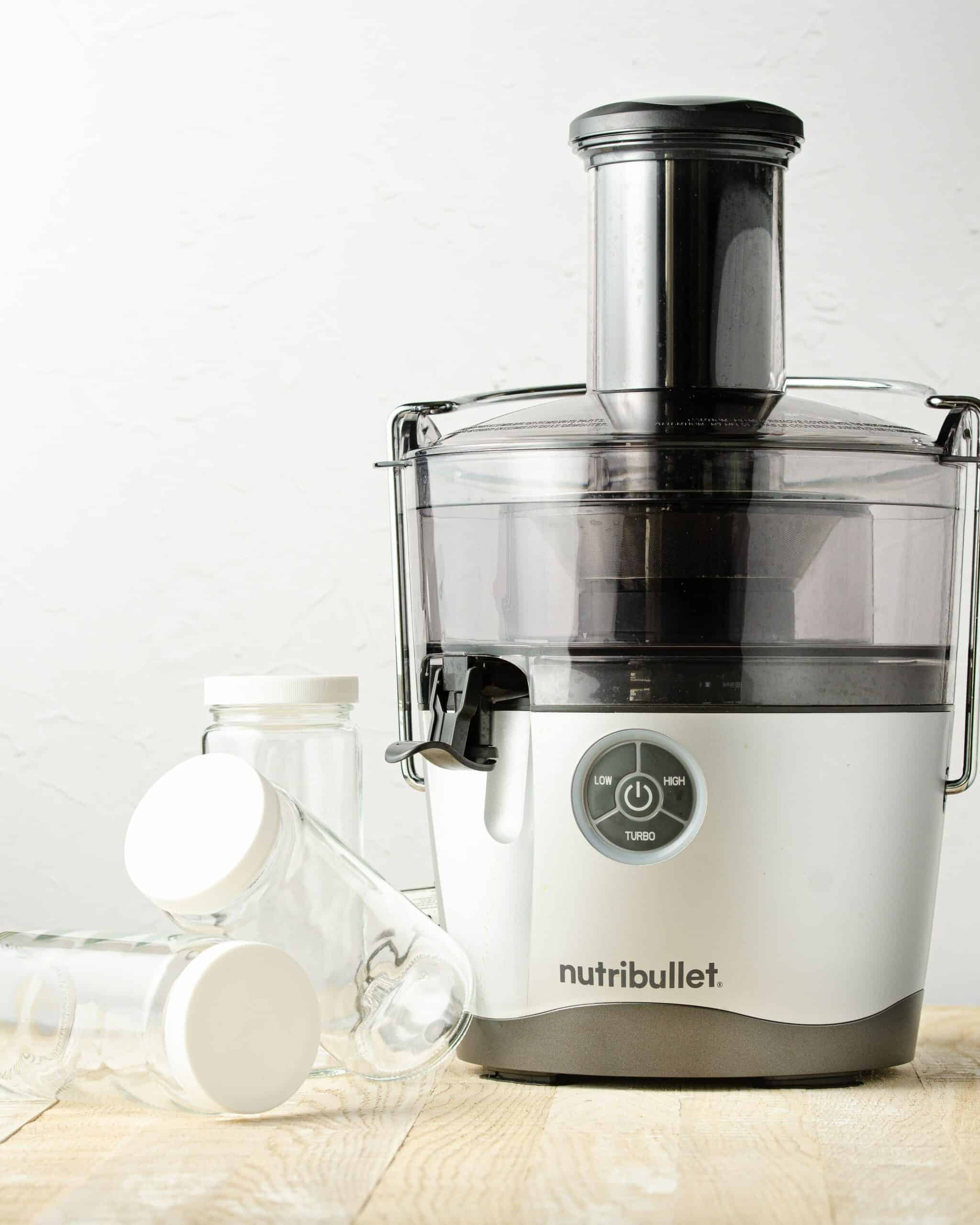 a Nutribullet Pro Juicer with three glass bottles for homemade juice to the left side