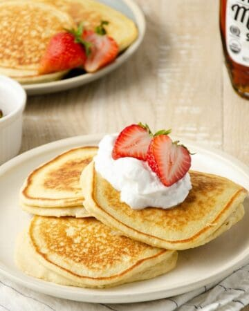 three oat milk pancakes layered on a plate topped with coconut whipped cream and halved strawberries. A small plate of pancakes sits to the back left with a small bottle of maple syrup sits behind.