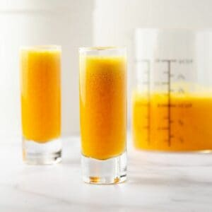 featured image of ginger turmeric shots poured out in shot glasses with a container of spoons, a bag of turmeric, and a measuring cup of the leftover ginger turmeric juice in the background.