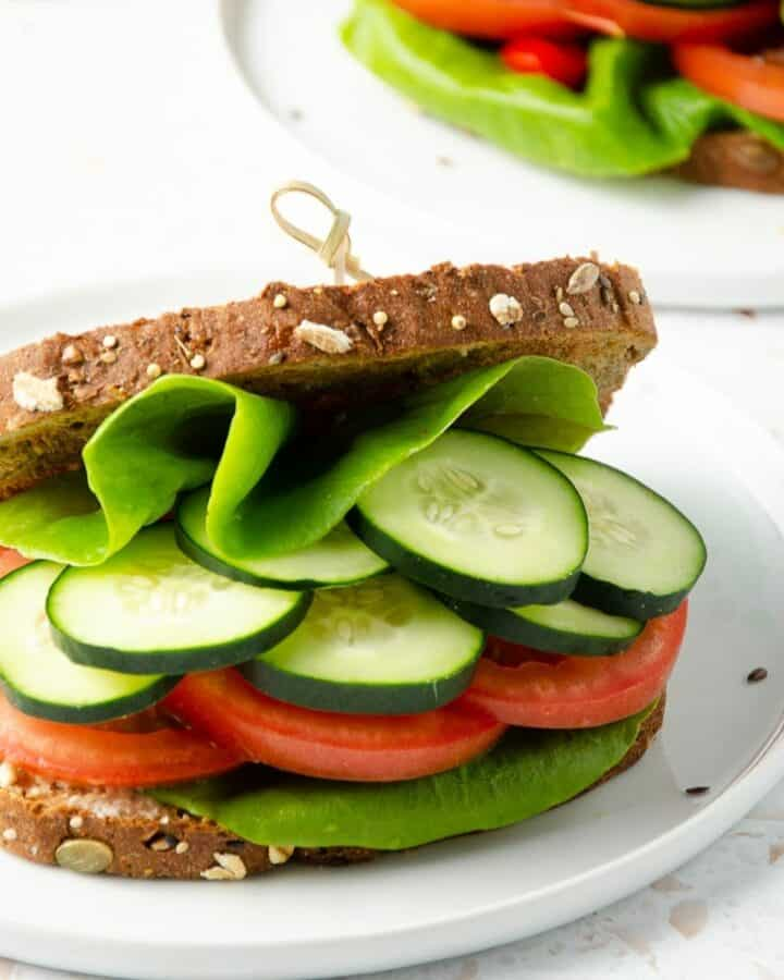 square feature photo of close up of a panera mediterranean veggie sandwich filled with butter lettuce, cucumber, tomato slices with a second sandwich and cutting board with fresh cucumber slices in the background.