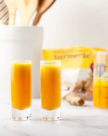 ginger turmeric shots poured out in shot glasses with a container of spoons, a bag of turmeric, and a measuring cup of the leftover ginger turmeric juice in the background.