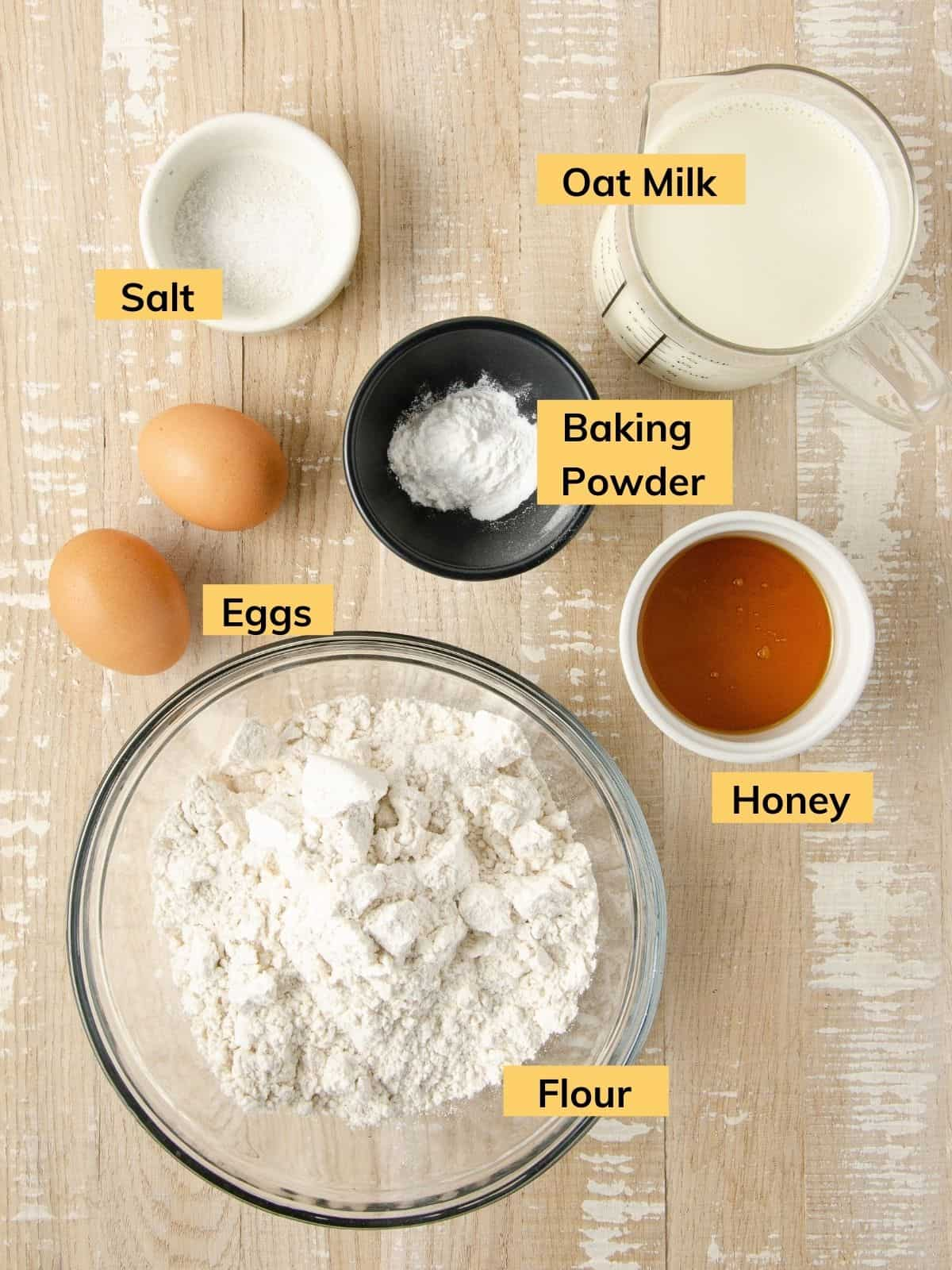 ingredients prepped for pancakes: gluten free flour in a glass bowl, a ramekin of honey, a black bowl of baking powder, two eggs, a small bowl with salt, and a measuring cup filled with oat milk