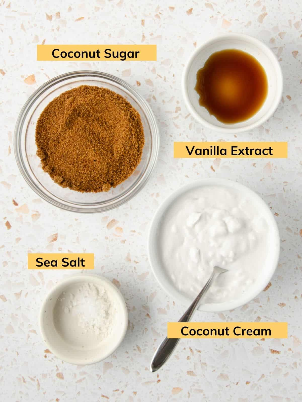 Ingredients for vegan salted caramel: a bowl of coconut sugar, a bowl of vanilla extract, a bowl of coconut cream, and a bowl of sea salt.
