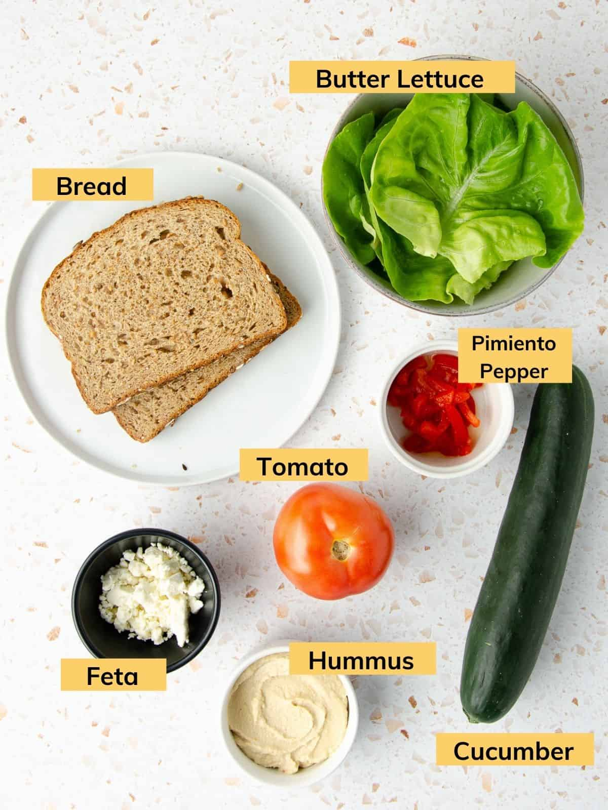 ingredients for a panera mediterranean veggie sandwich: a plate of bread slices, a bowl of feta, a bowl of hummus, one tomato, one cucumber, a bowl of butter lettuce and a small bowl of pimiento peppers