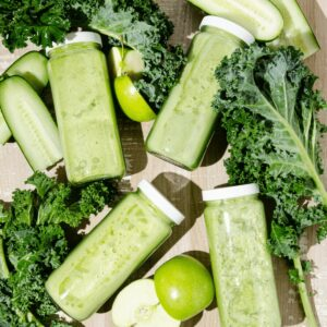 Featured Image of Four Glass bottles of green juice surrounded by chopped kale, green apples and cucumbers.