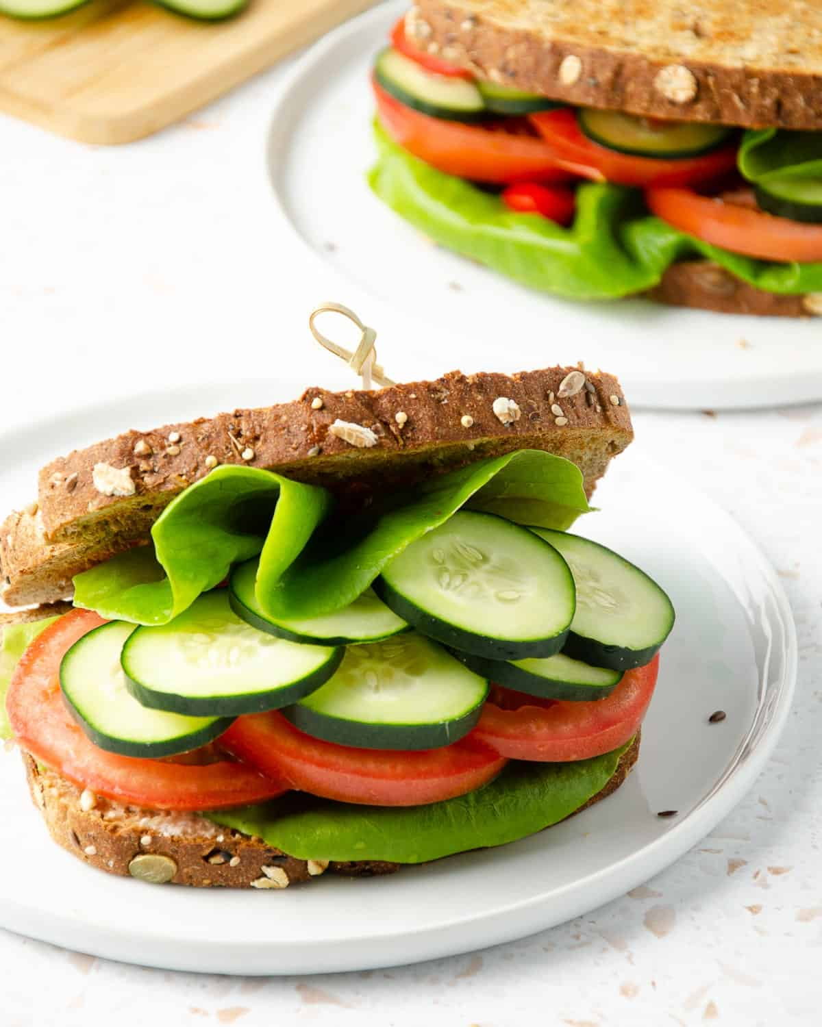 close up of a panera mediterranean veggie sandwich filled with butter lettuce, cucumber, tomato slices with a second sandwich and cutting board with fresh cucumber slices in the background.
