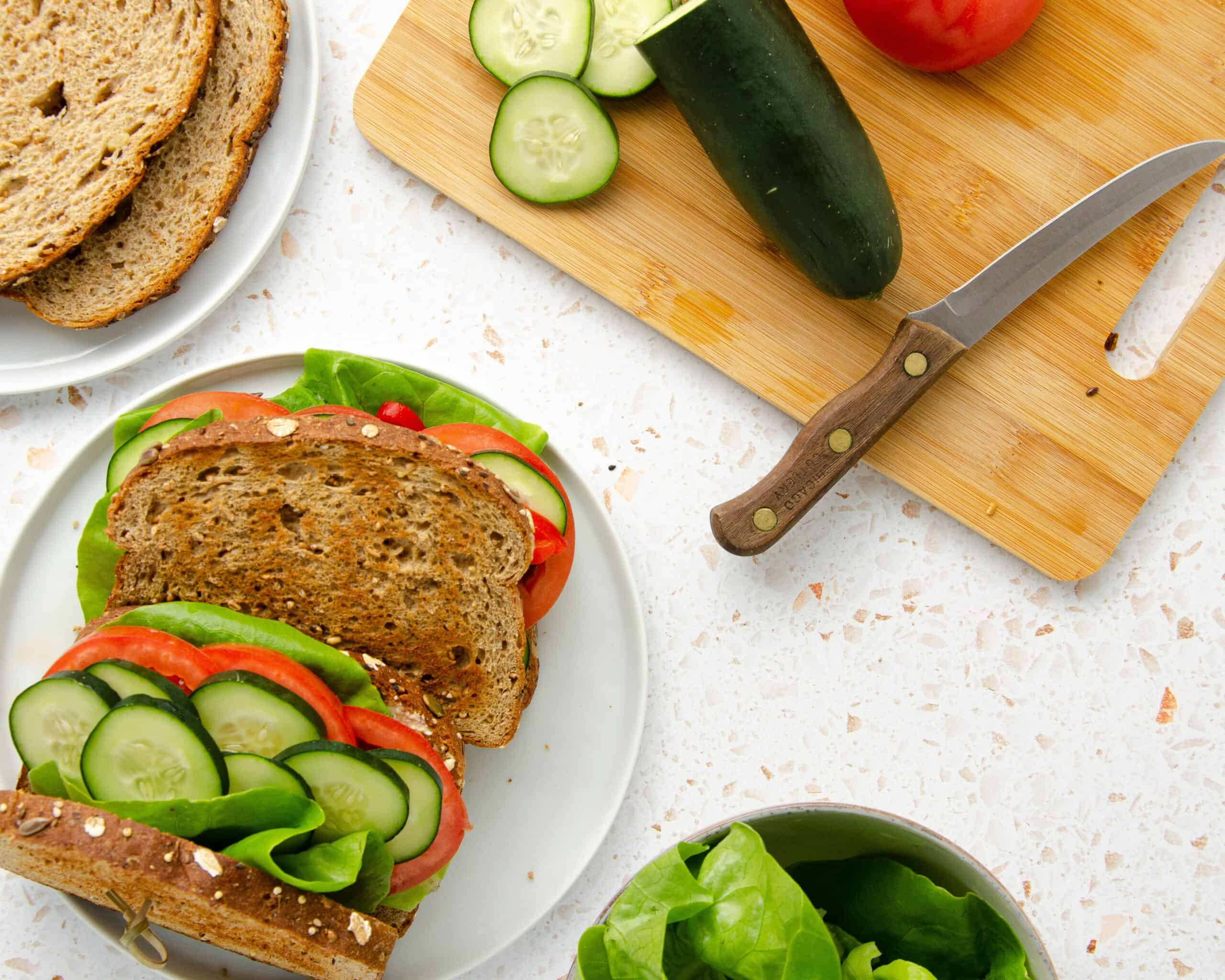 a plate of two panera mediterranean sandwiches with a bowl of butter lettuce, a plate of sandwich bread, and a cutting board of fresh sliced cucumbers and tomatoes surrounding it