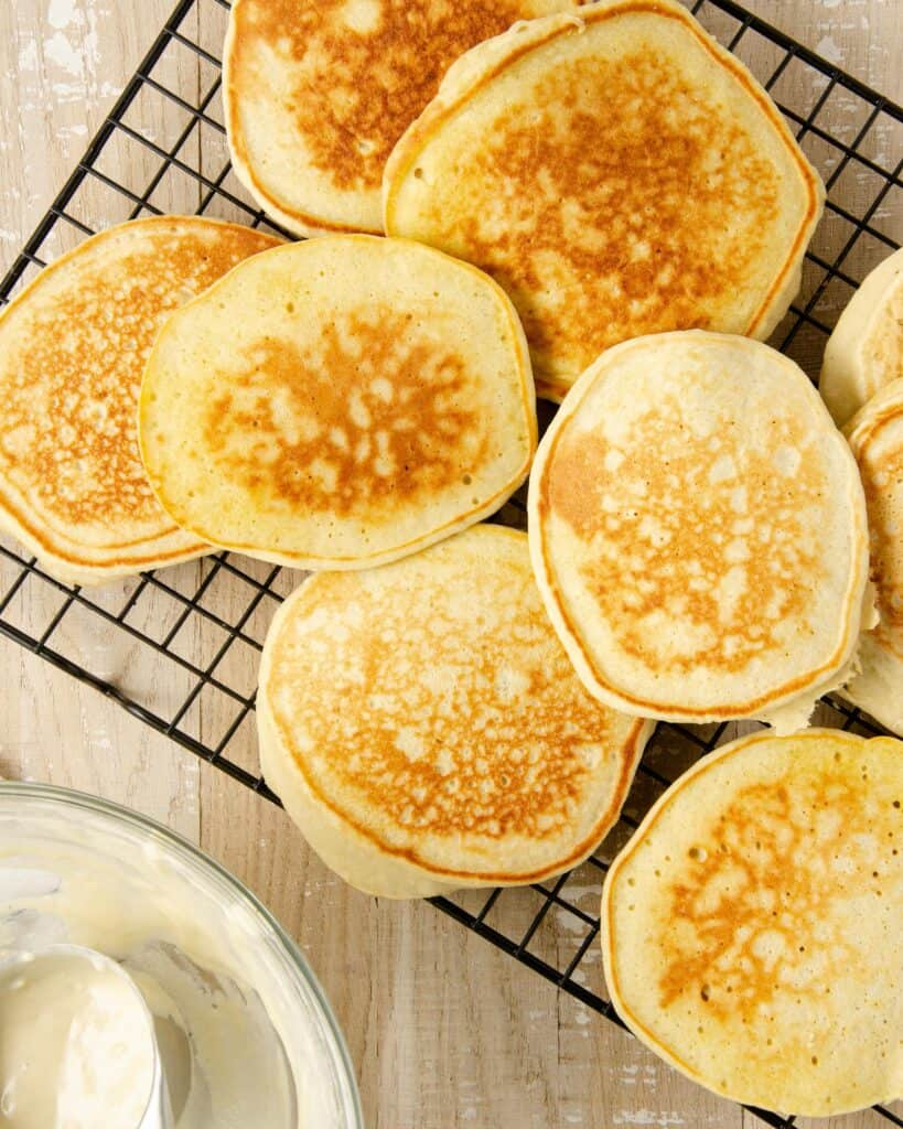 A cooling tray topped with cooked oat milk pancakes layered on top of each other. An empty bowl of pancake batter with a scoop to the side.